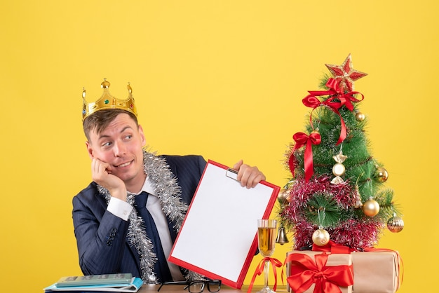 Вид спереди красивого мужчины с короной, сидящего за столом возле рождественской елки и подарков на желтом