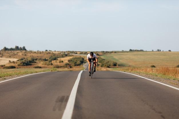 보호 헬멧 및 스포츠 의류에 잘 생긴 젊은 남자의 전면보기 적극적으로 아스팔트 도로에서 자전거를 타고