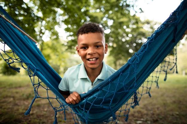 ハンモックで幸せな少年の正面図