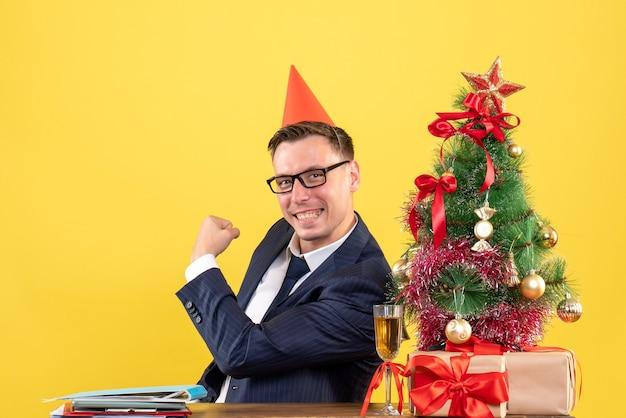 クリスマスツリーの近くのテーブルに座って、黄色でプレゼントパーティーキャップと幸せなビジネスマンの正面図