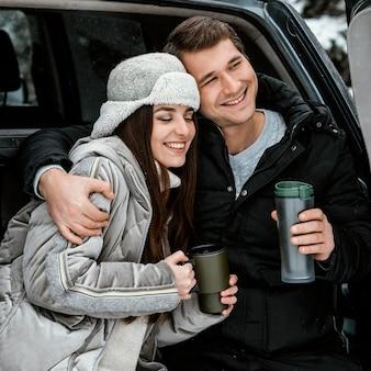 Вид спереди счастливой пары, пьющей теплый напиток в багажнике автомобиля во время поездки