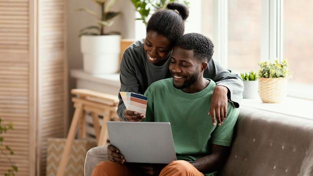 집을 재 장식 할 계획을 만드는 소파에 행복한 커플의 전면보기