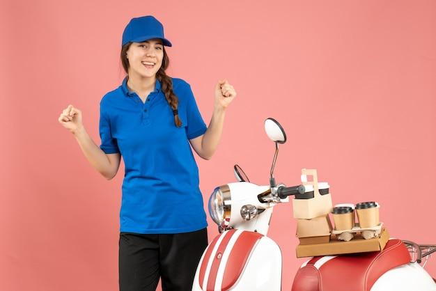 Вид спереди счастливой дамы-курьера, стоящей рядом с мотоциклом с кофе и небольшими пирожными на нем на фоне пастельного персикового цвета
