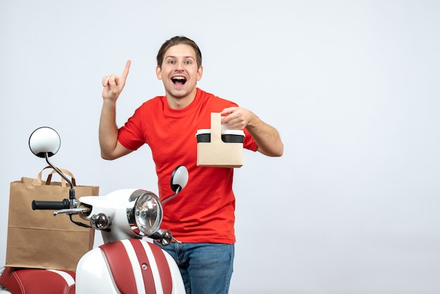 白い背景の上に上向きの順序を示すスクーターの近くに立っている赤い制服を着た幸せな配達人の正面図