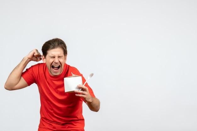 白い背景の上の紙箱とスプーンを保持している赤いブラウスで幸せな感情的な若い男の正面図