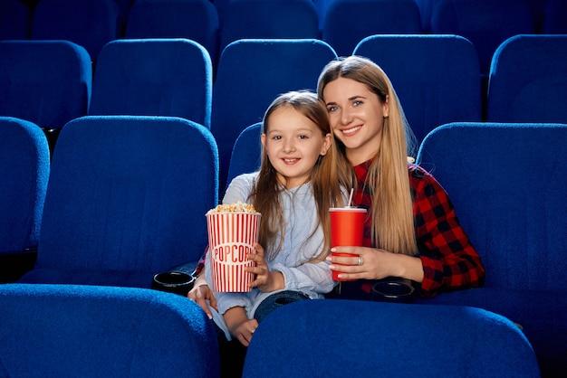 Вид спереди счастливой семьи, проводящей время вместе в пустом кинотеатре