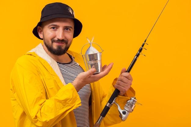 釣り竿を持って幸せな漁師の正面図