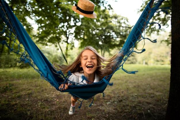 ハンモックで幸せな女の子の正面図