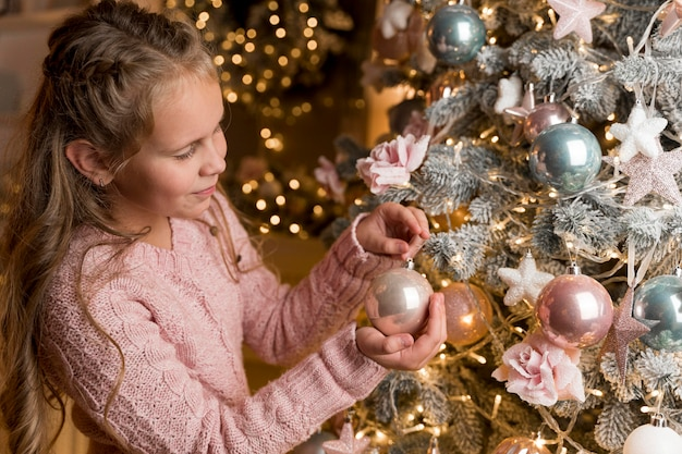 Вид спереди счастливой девушки с подарками и елкой