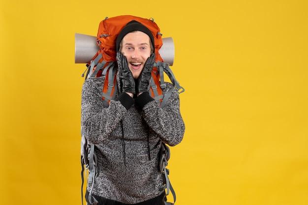 彼の顔に手を置いている革手袋とバックパックを持つ幸せな男性のヒッチハイカーの正面図