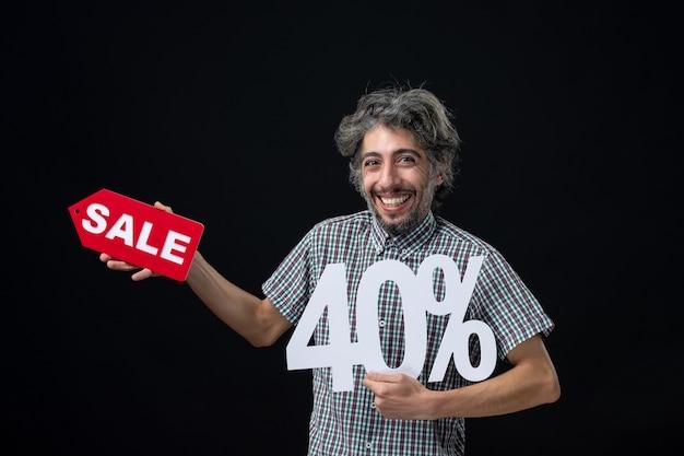 黒い壁にマークと販売サインを掲げている幸せな男の正面図