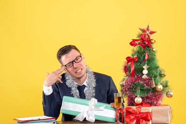 クリスマスツリーの近くのテーブルに座っている彼の寺院に指銃を置き、黄色で提示する幸せな男の正面図