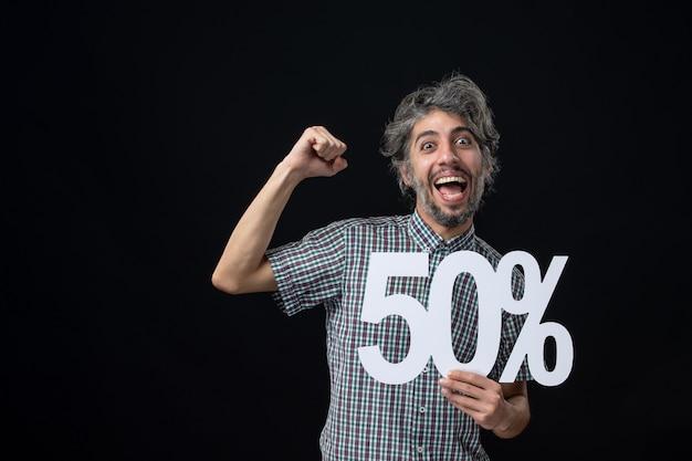Вид спереди счастливого человека с выражением победителя, держащего знак на темной стене