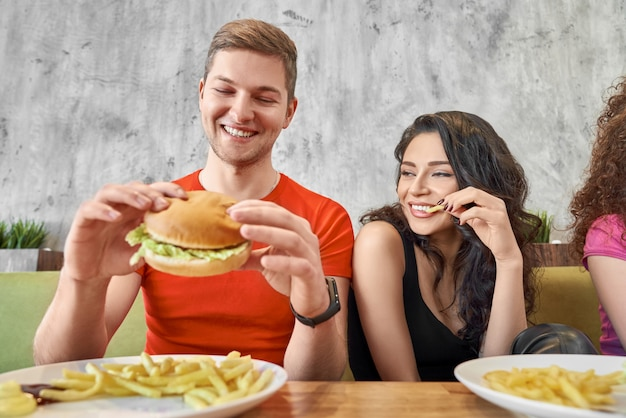 Вид спереди счастливой пары едят фаст-фуд в кафе