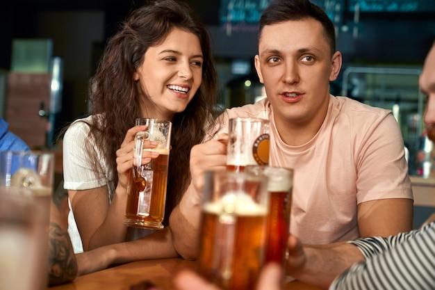 술집에 함께 앉아 맥주를 마시고 친구와 이야기하는 행복 한 쌍의 전면 모습. 예쁜 여자와 남자는 휴식을 즐기고, 웃음과 카페에서 농담. 여가와 재미의 개념.