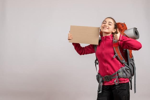 Вид спереди счастливой красивой женщины с большим рюкзаком, держащей картон, показывая пальцы вверх