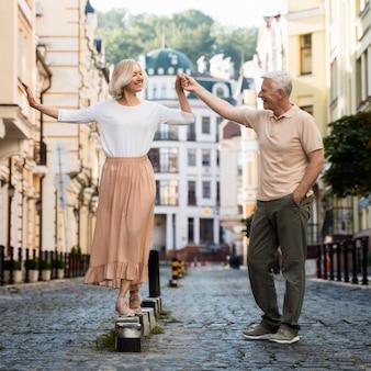 屋外散歩を楽しんで幸せな先輩カップルの正面図