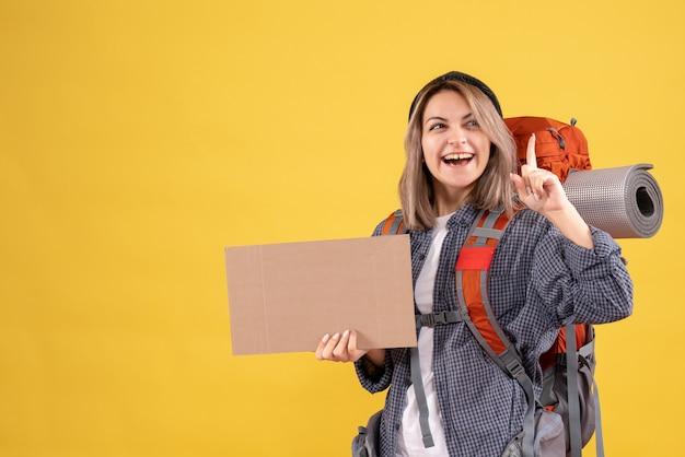 段ボールを保持しているバックパックと幸せな旅行者の女性の正面図