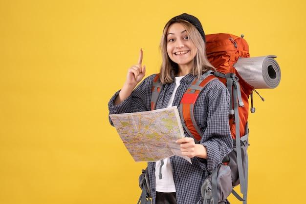 アイデアで驚くべき地図を保持しているバックパックを持つ幸せな旅行者の女性の正面図