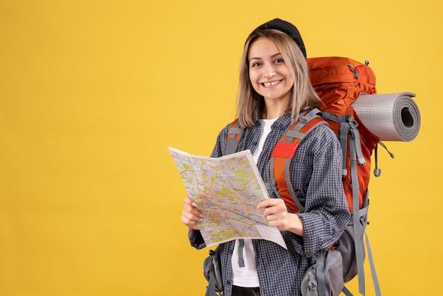Вид спереди счастливой женщины-путешественницы с рюкзаком, держащим карту