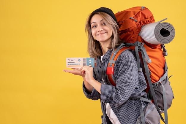 チケットを保持しているバックパックと幸せな旅行者の女性の正面図