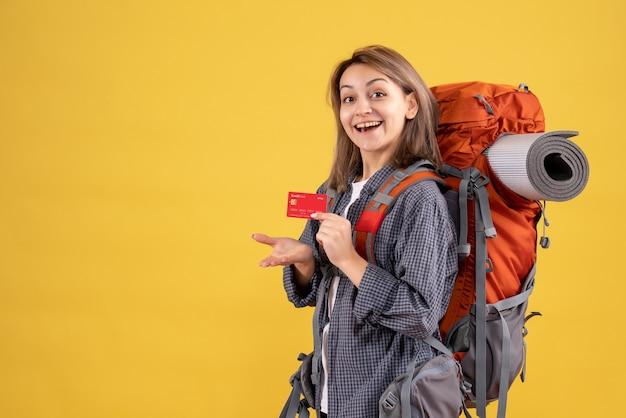 カードを保持している赤いバックパックと幸せな旅行者の女性の正面図