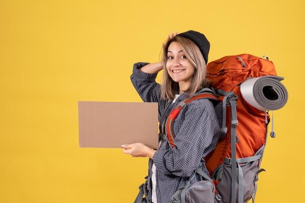 段ボールを保持している赤いバックパックと幸せな旅行者の女性の正面図