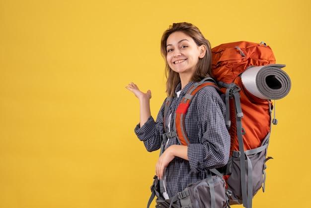壁を指している赤いバックパックと幸せな旅行者の女性の正面図