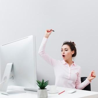 コンピューターでの作業中に良いニュースを見つける幸せな女性の正面図