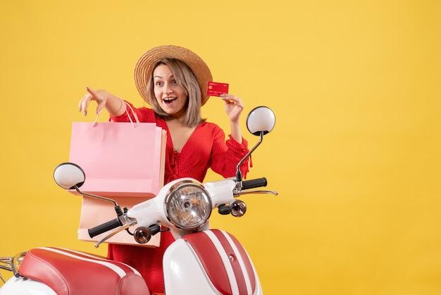 쇼핑 가방과 뭔가 가리키는 카드를 들고 오토바이에 빨간 드레스에 행복 한 여자의 전면보기
