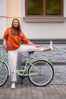 Вид спереди счастливой женщины, позирующей со своим велосипедом снаружи