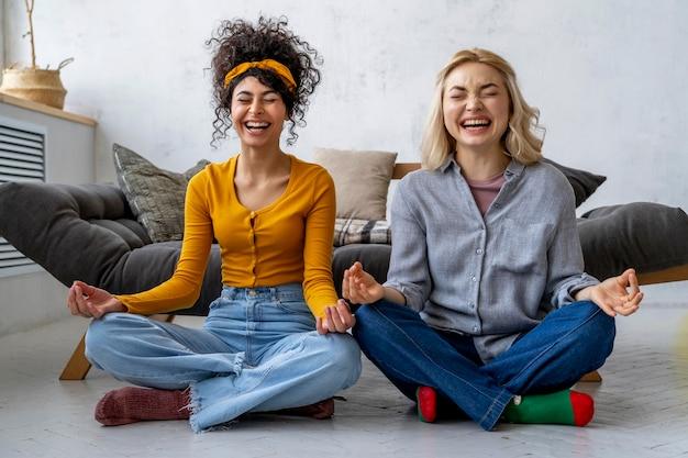 Вид спереди счастливых женщин, смеющихся и занимающихся йогой