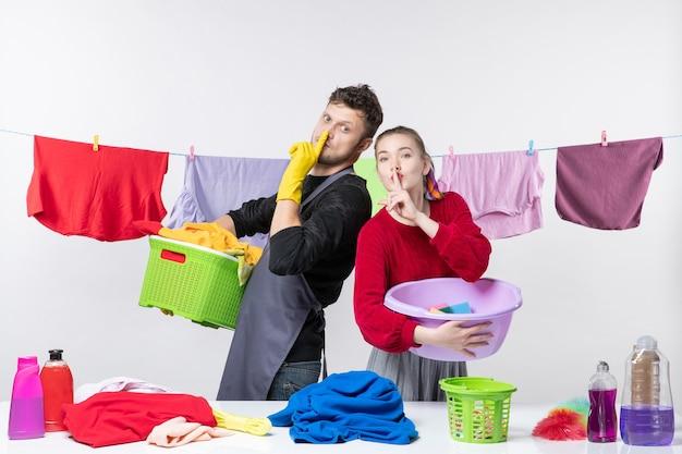 Вид спереди счастливой молодой пары, делающей знак тишины, держа в руках стиральные средства на белой стене