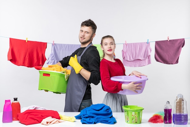 Вид спереди счастливой молодой пары человека, показывающего большой палец вверх, и его жены, держащей умывальник на белой стене