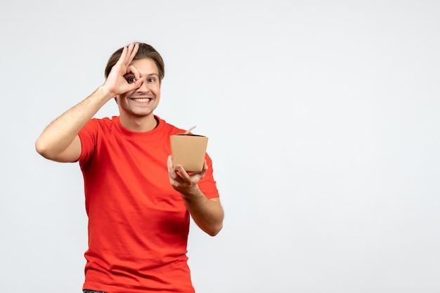 小さな箱を保持し、白い背景の上の眼鏡ジェスチャーを作る赤いブラウスで幸せな若い男の正面図