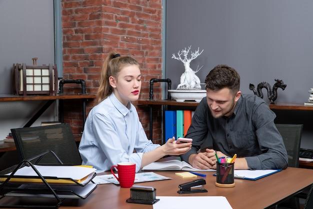 幸せな若い男性と彼の女性の同僚がオフィス環境で1つの問題を議論しているテーブルに座っている正面図