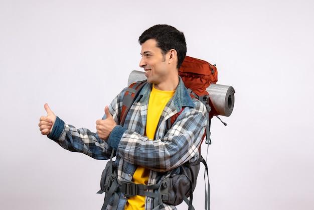 親指をあきらめてバックパックと幸せな若い男の正面図
