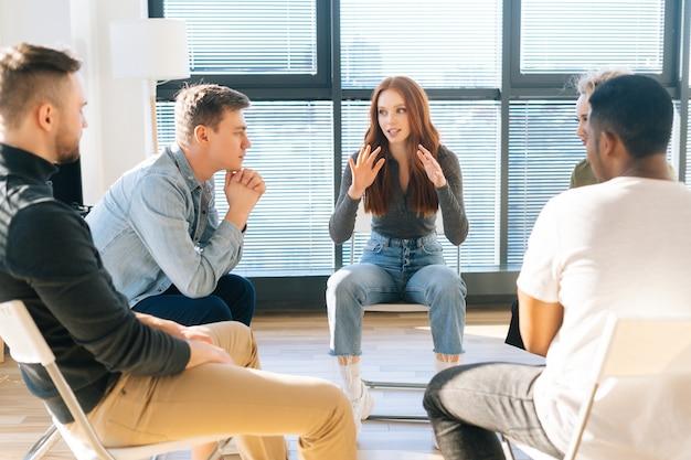 화창한 날 창가에 있는 현대적인 사무실에서 창업 프로젝트에 대한 브레인스토밍을 하는 동안 행복한 젊은 빨간머리 여성 사업가가 창의적인 비즈니스 팀과 새로운 아이디어에 대해 이야기하고 토론하는 모습.