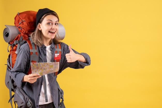 Вид спереди счастливого молодого путешественника с рюкзаком, держащего карту, показывает палец вверх