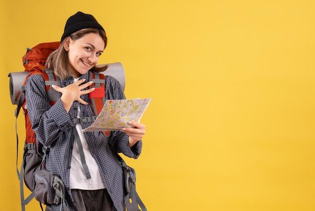 黄色の壁に地図を保持しているバックパックと幸せな若い旅行者の正面図