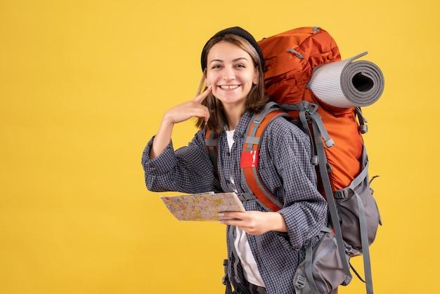 彼女の笑顔を指している地図を保持しているバックパックと幸せな若い旅行者の正面図