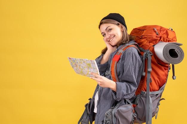 黄色の壁に立っている地図を保持しているバックパックと幸せな若い旅行者の正面図