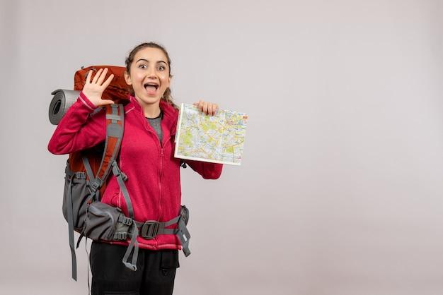 灰色の壁に誰かを歓迎する地図を保持している大きなバックパックと幸せな若い旅行者の正面図