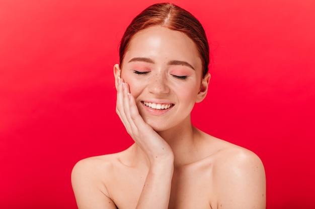 目を閉じて笑っている幸せな若い女性の正面図。赤い背景でポーズをとって裸の生姜の女の子。