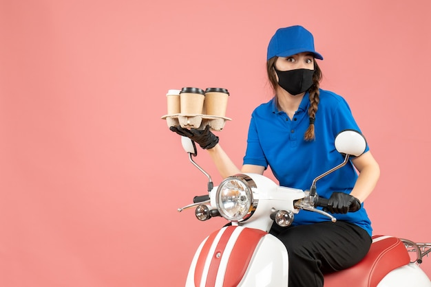 パステルピーチの背景に注文を保持しているスクーターに座っている医療用マスクと手袋を身に着けている勤勉な宅配便の女性の正面図