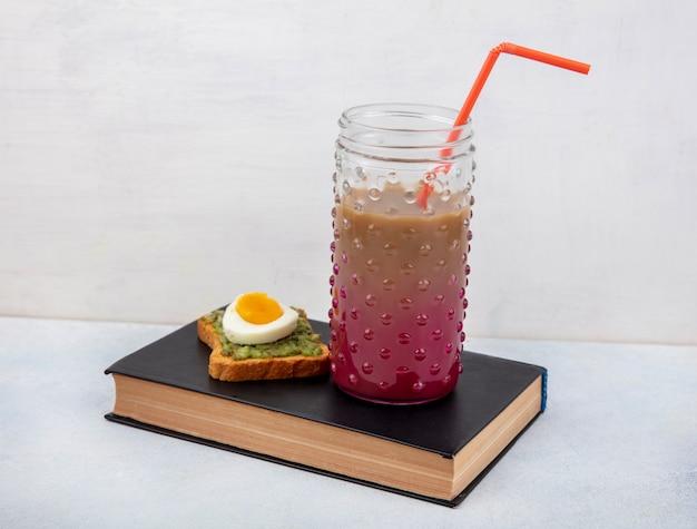 Вид спереди здорового авокадо на ломтик хлеба с яйцом и коктейль в стеклянной банке над книгой на белой поверхности