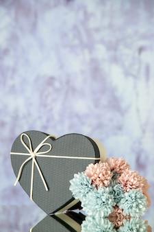 自由空間と灰色の抽象的な背景の上のハートボックス色の花の正面図