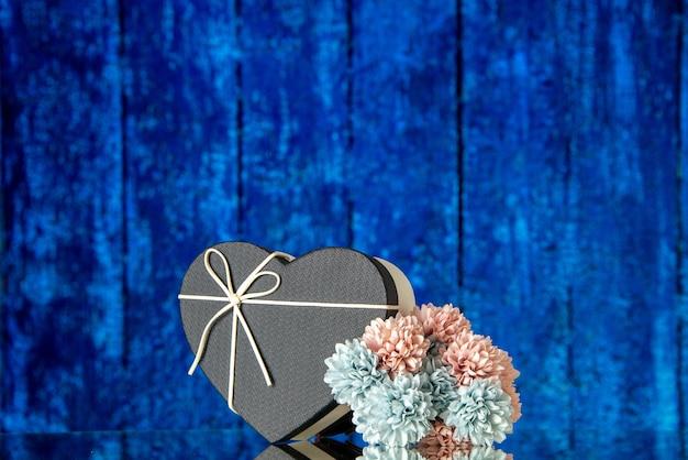 青い木製の背景の空きスペースに黒いカバー色の花とハートギフトボックスの正面図