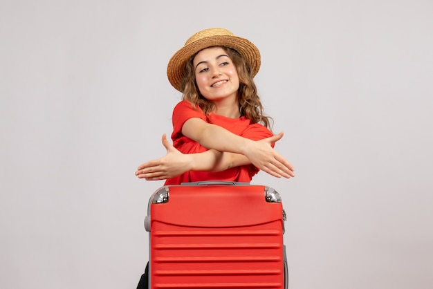 白い壁に立っている手を与える彼女のスーツケースと休日の女の子の正面図