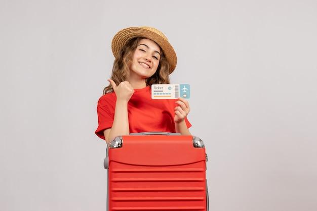 親指をあきらめてチケットを保持している彼女のスーツケースと休日の女の子の正面図